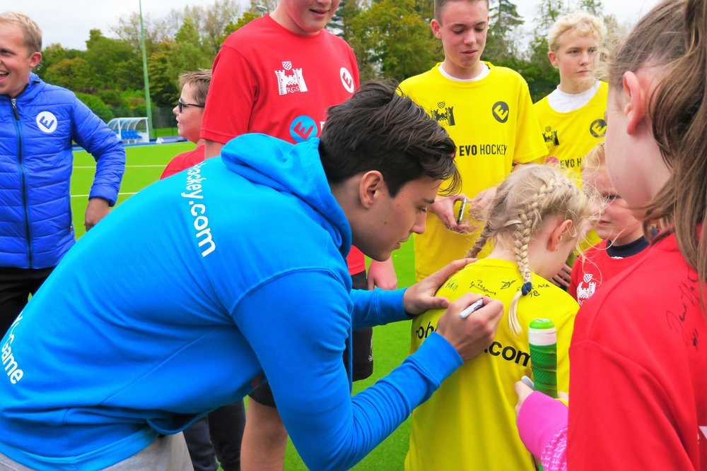 International hockey players signing autographs at an EVO camp