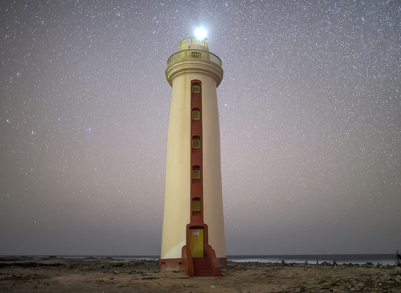 A star-crowded sky behind Willemstoren Lighthouse