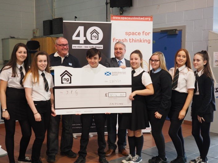 Youngsters get presented with a cheque with ng homes Board Members, John Thorburn and Richard Porter