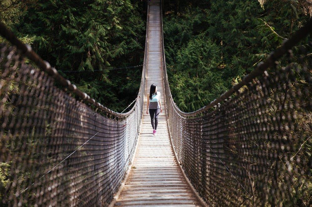 negative-space-woman-walking-swing-bridge-burst.jpg
