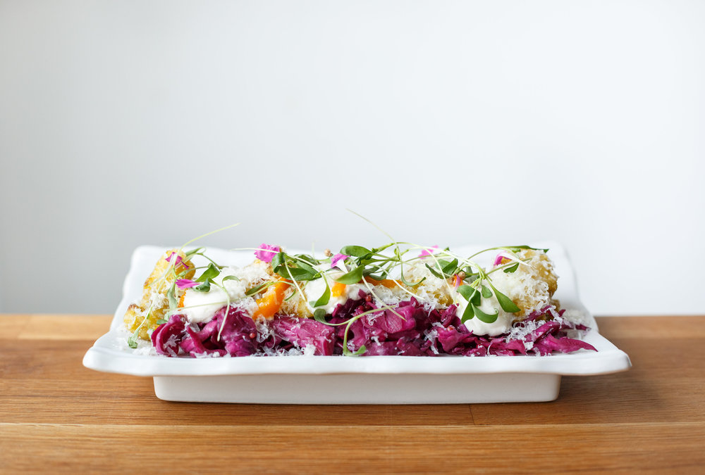 "Cauliflower ""Chilaquiles"" green cabbage, manchego creama, fermented jalapeno and chive blossom hot sauce"