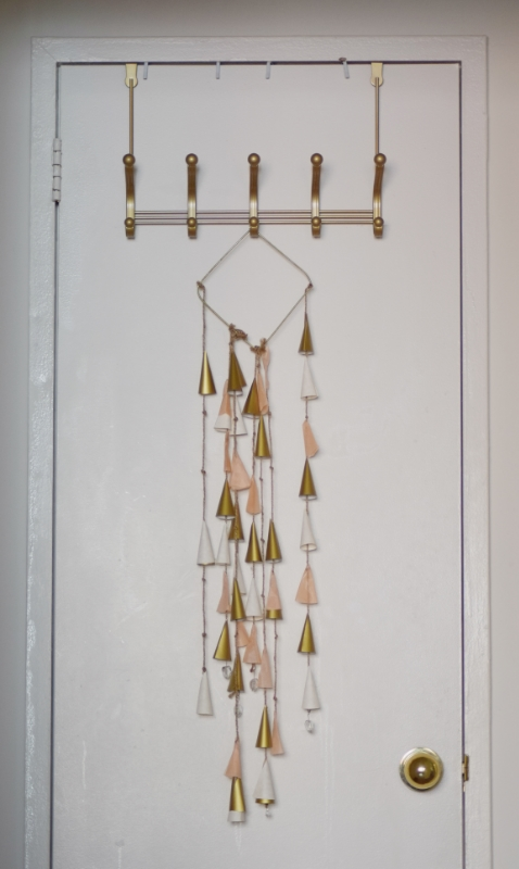 I hate the look of a bare coat rack...it feels too utilitarian to me. I like to add some kind of art, like this paper and string mobile. Coats and bags can be hung right over the top of it!