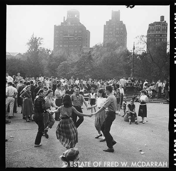 Watched by an audience a circle of three man and three women hold hands as they dance together in Washington Square Park, New York, New York, July 1951.