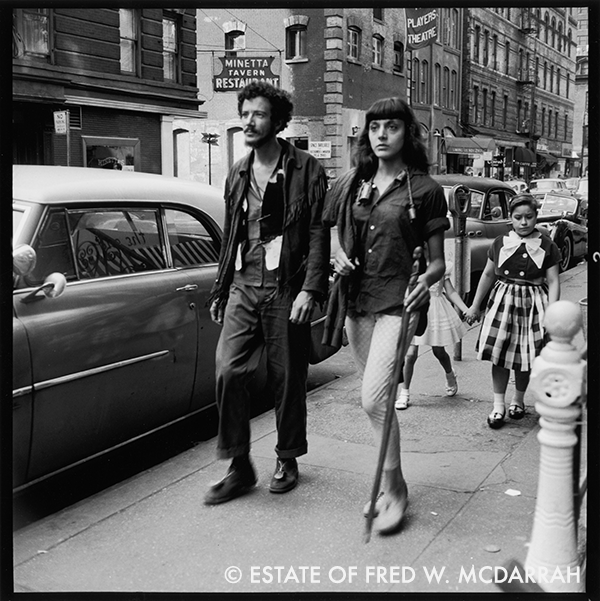 American author Ambrose Hollingworth Redmoon (1933 - 1996, born James Neil Hollingworth) and his companion, identified only as Louise, walk along MacDougal Street (just past the intersection with Minetta Lane), New York, New York, June 21, 1959. Redmoon later became the manager of the rock group Quicksilver Messenger Service and, after suffering a near fatal injury in a car crash, became an author. Visible in the background are the Minetta Tavern and the Players Theatre.