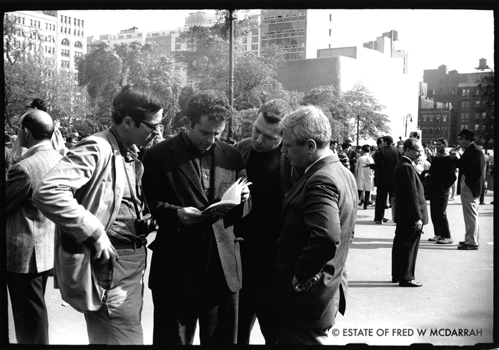 American author Norman Mailer (1923 - 2007) (second left) looks at Fred McDarrah's book 'The Beat Scene' with McDarrah (1926 - 2007) (left), author, editor, and Paris Review co-founder Doc Humes (born Harold Louis Humes Jr, 1926 - 1992) (second left), and Marvin Frank (right) in Washington Square Park, New York, New York, May 15, 1960.