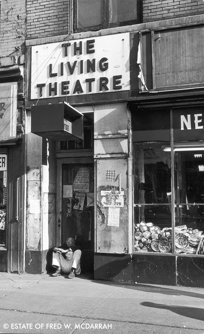 The entrance to the boarded up Living Theater, where a man sleeps in the doorway, 69 West 14th St.,, October 20, 1965. The sign on the door reads, in part, 'The Living Theatre has been taxed out of existence by the US Gov't. Send your complains to' followed by an obscured name and the address of the Federal Court House in Foley Square.