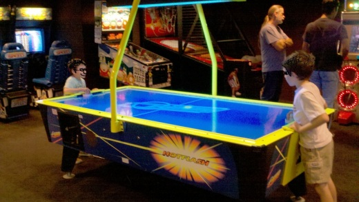 Kids in disguise playing air hockey in the arcade at the Muvico Theater