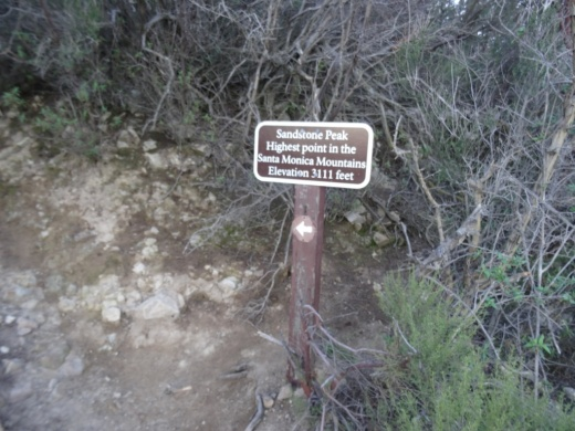 There are some steps, then some trekking, to reach the top from this sign. You've made it!