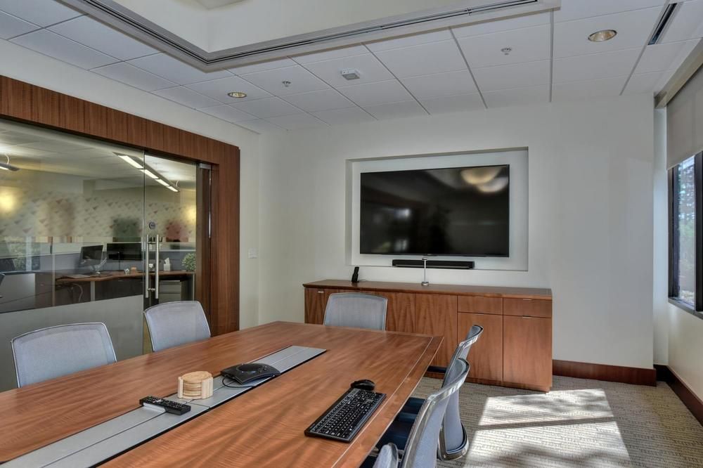 Executive boardroom with Sony 75-inch 4K UHD TV and on-wall Sonos Playbar soundbar