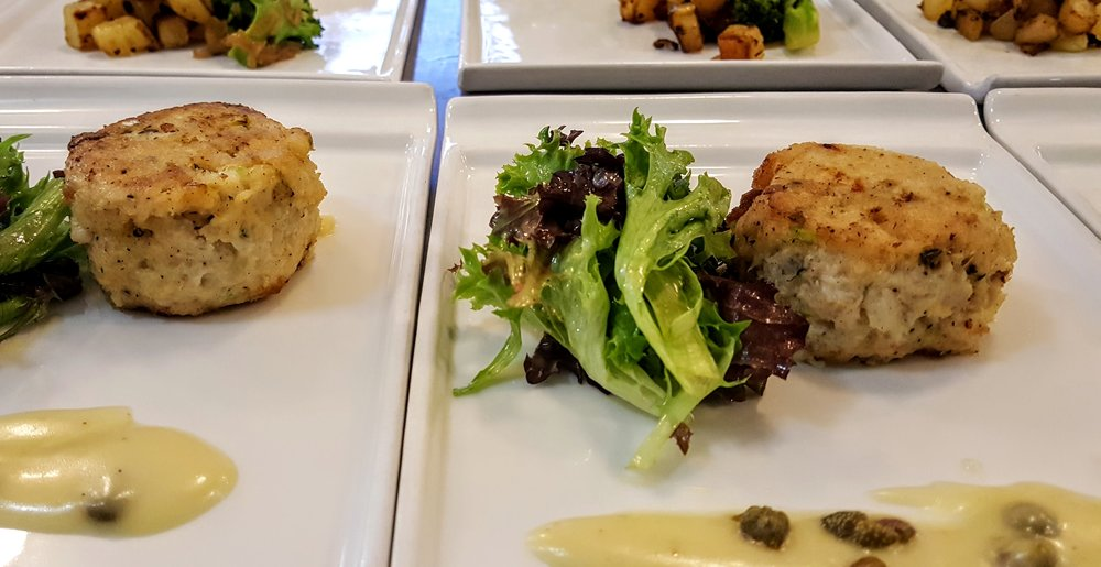 Dungeness Crab Cake  Crispy Yukon Gold potatoes, broccoli with caramelized onions, lemon caper vinaigrette