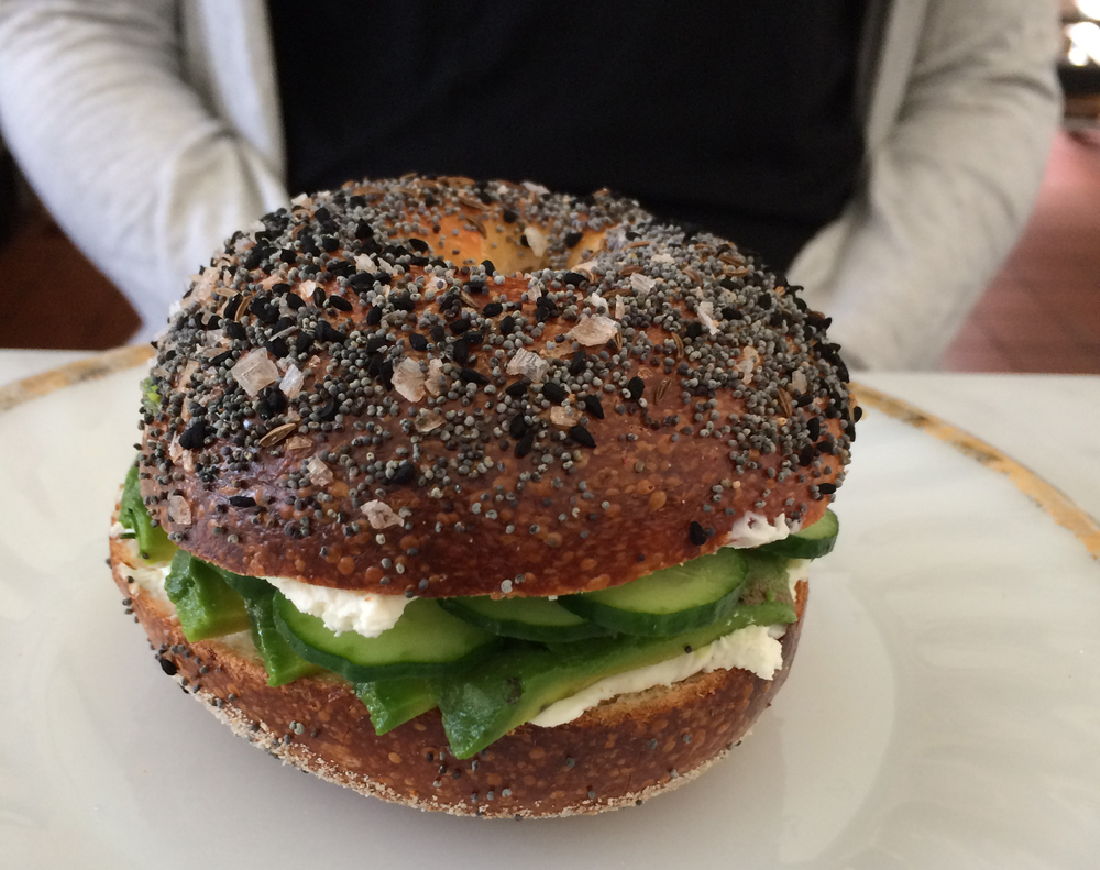 An everything (poppy seed, sea salt, and nigella seed) bagel filled with cream cheese, avocado, cucumber, and chives.