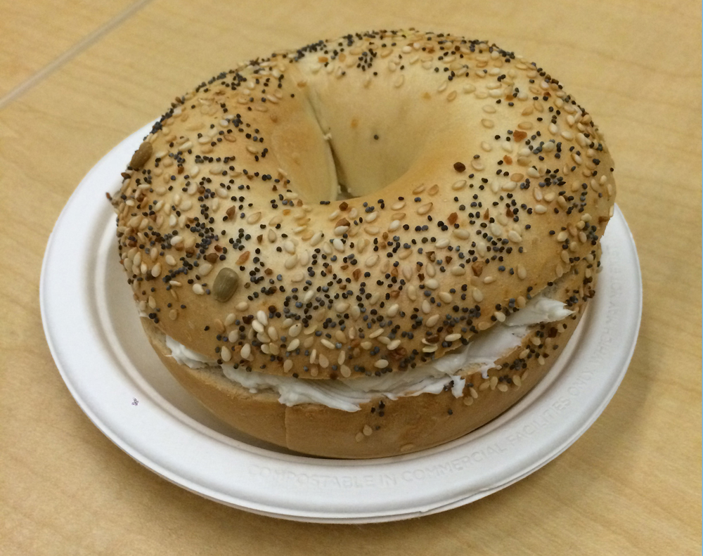 An everything bagel with cream cheese, unnervingly similar in color to the conference room table.
