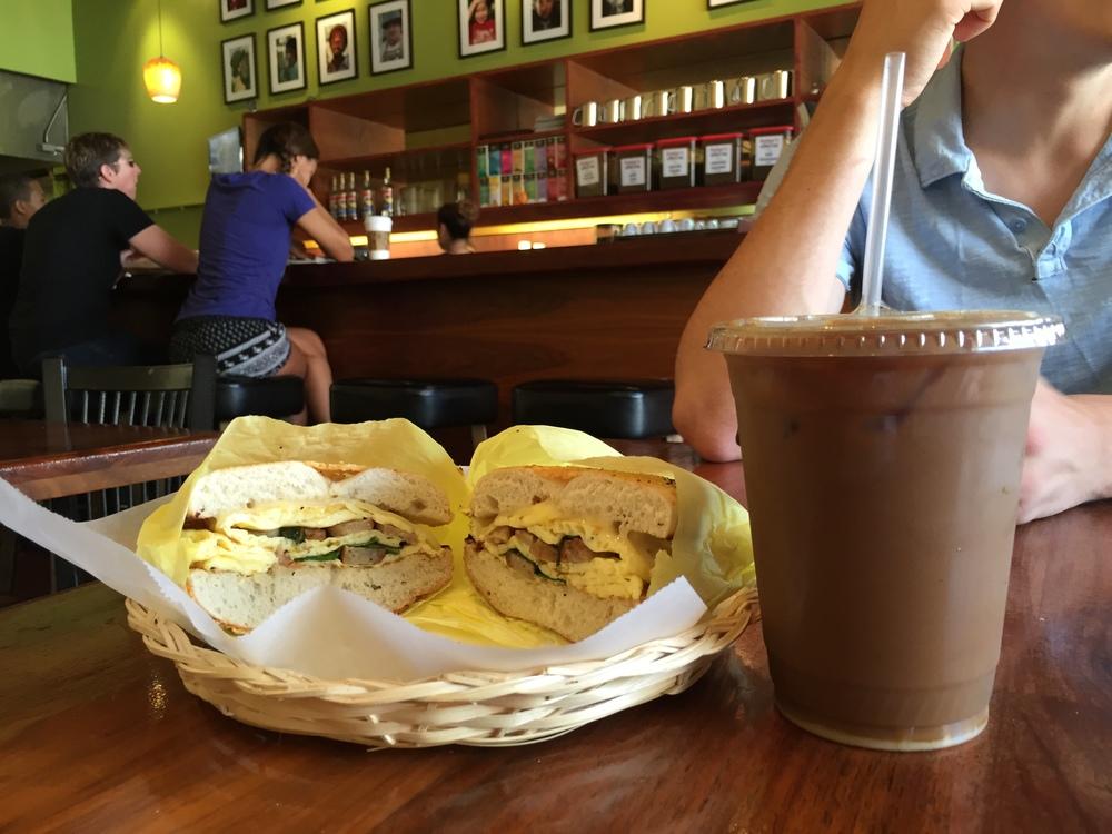 Luke's sausage, egg, and basil sandwich, accompanied by iced coffee.