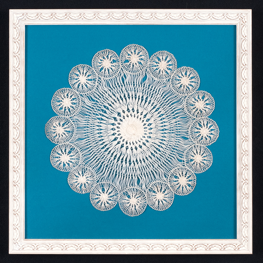 This doily is hand stitched to an acid free mat.Glass spacers are used to lift the ultra violet protective glass off the surface.The frame is a white painted moulding with a floral design. Photo Credit: Elizabeth LaJeunesse.