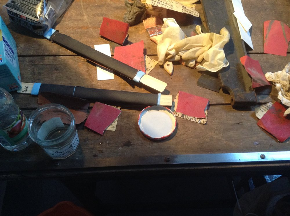 Piles of sandpaper from sanding the rust of the blade.
