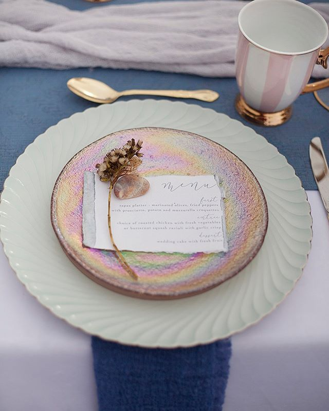 This dusty blue and pink beach styled shoot is featured on @so_thisislove! I love the soft muted colors and romantic Florals. I used hand made paper for the stationery and dip dyed the edges with a dusty blue. Link in bio for the full feature! Planning: @linakreisbergpl Photography: @sarajdsign  Wedding dress: @marina_semone Florals: @rosewoodfloralco  Table linens: @wisteria_and_vine