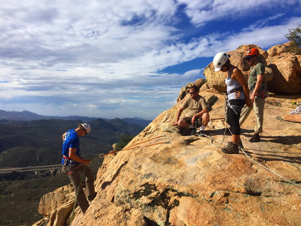 AAC Instructors Piotr An (blue shirt) and Tom Vokes (orange helmet) discuss rappelling basics with AAC Members Toby Hutchens and Melissa Angeles. Photo cred: Jonathan Wachtel