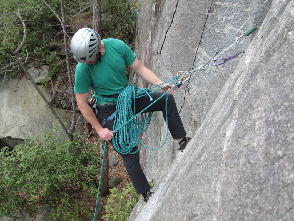 A modern belayer does not just use an anchor as a backup.  As we can see, this belayer is fully committed to the load-bearing properties of the anchor.  It holds his bodyweight, and the bodyweight of his second.