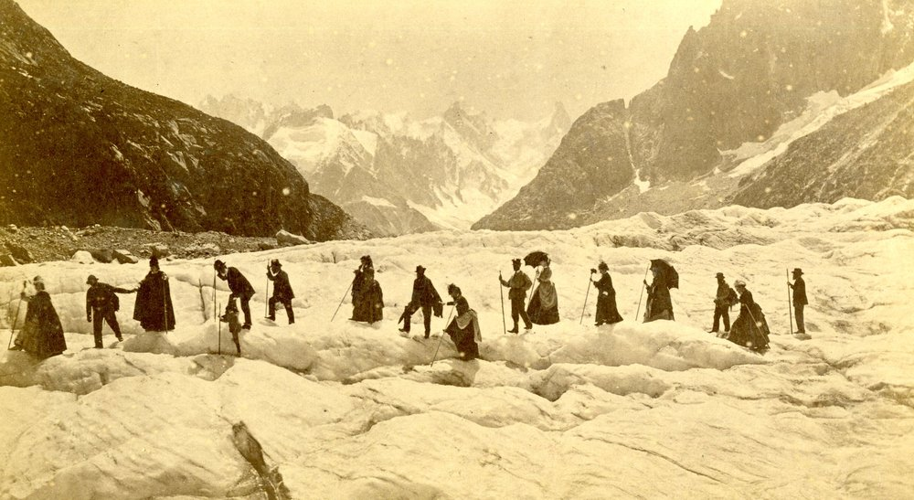 A party of mountaineers crossing a glacier in the 1870's or 1880's. The leader of the party used a hand axe to cut steps into the snow - the rest of the party used alpenstocks for balance.