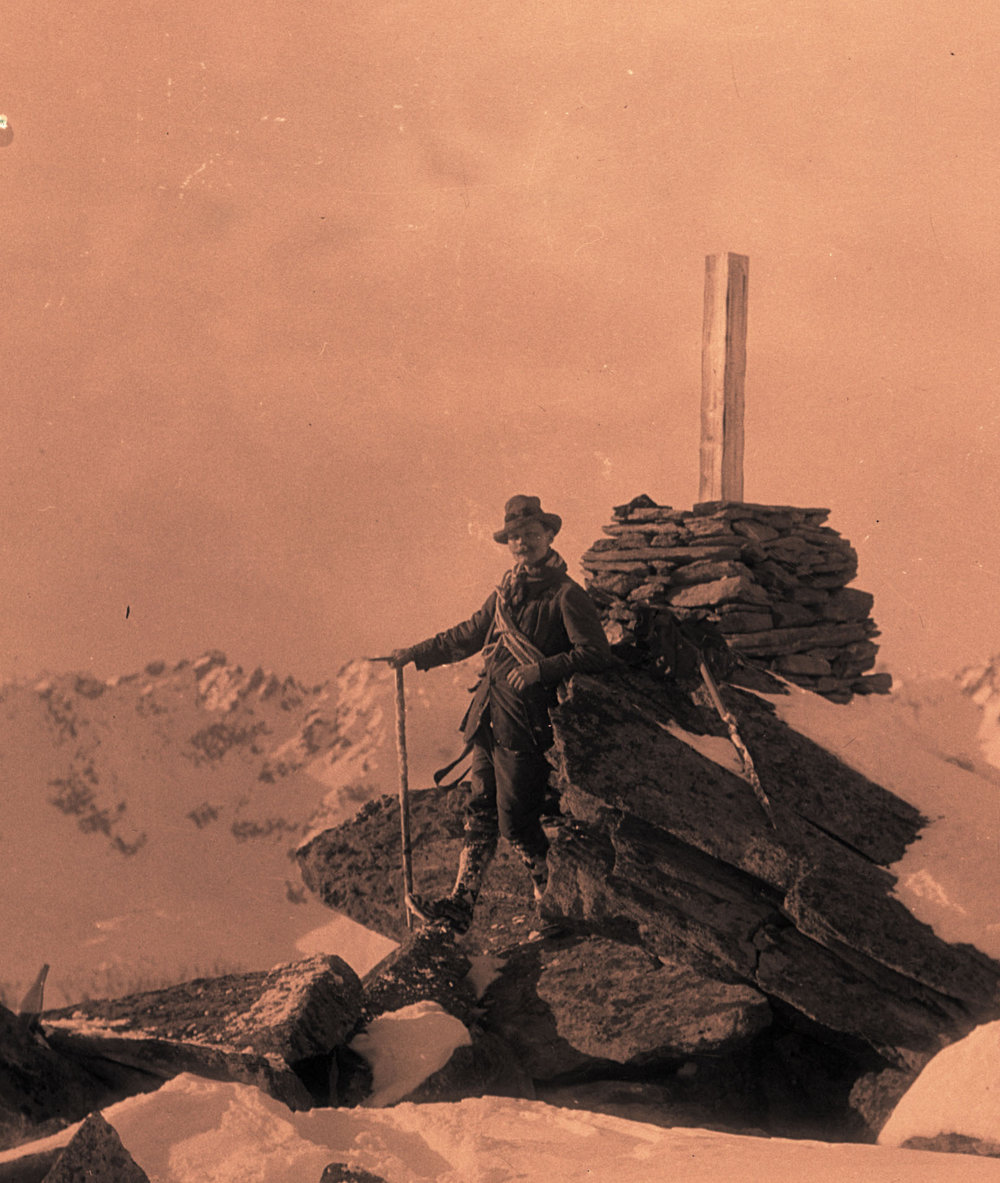 Andrew James Gilmour posing with an ice axe on a summit.