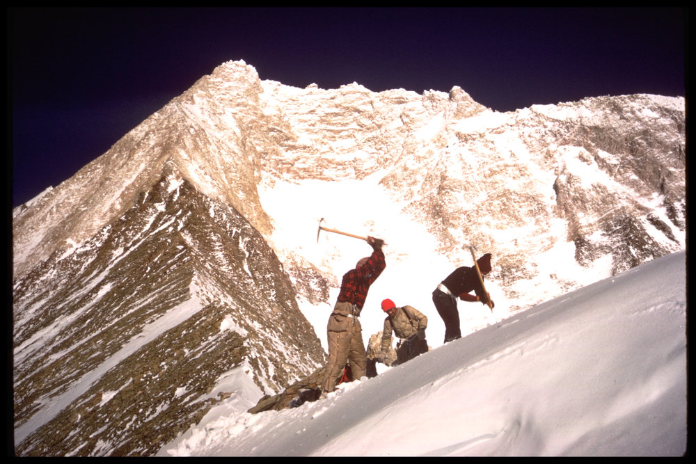 These mountaineers are cutting a tent platform with their ice axes