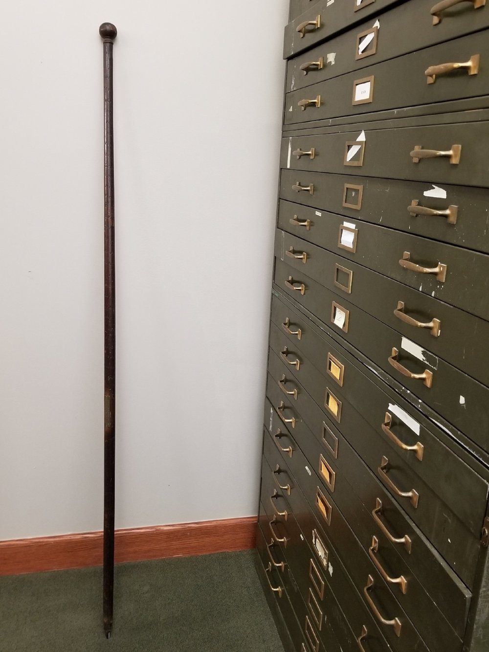 This alpenstock is of the oldest variety. It stands about five and a half feet tall and has a sharp metal spike at the bottom.