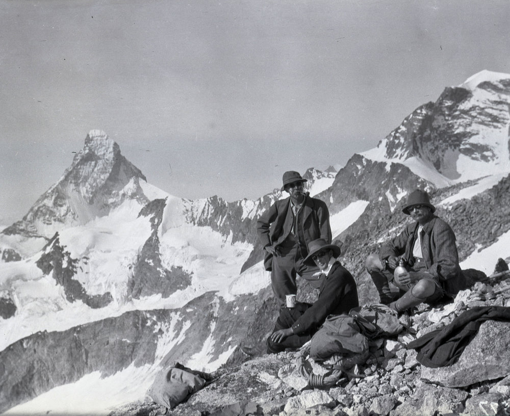 Three men pause for refreshment while climbing in the Alps. The Matterhorn in the background.