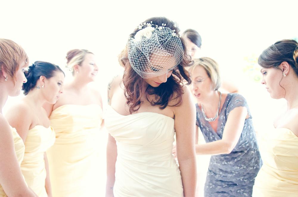 charleston wedding photography photographer bride putting on dress mother of the bride bridesmaids prewedding wedding prep.jpg