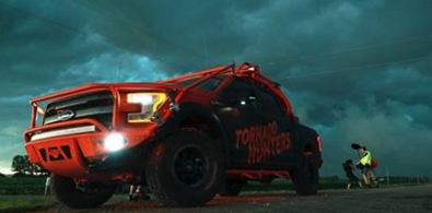 "A large orange and black pickup truck with ""Tornado Hunters"" on the side stands on the side of a rural road near where men are taking photos of the dark green-grey skies above them. Photo from the Tornado Hunters Facebook page."