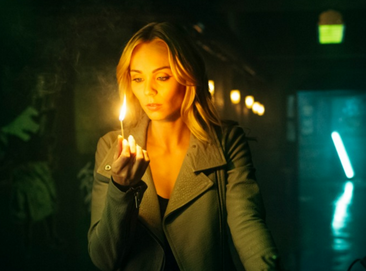 Elena Michaels (Laura Vandervoort) stares at the flame on a long lit match. From the Space.ca site.