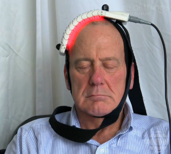 A man with his eyes closed wears a flat, flexible appliance on his head, from the top to part of the right side. The appliance emits a reddish light underneath. Image links to source at cbc.ca.