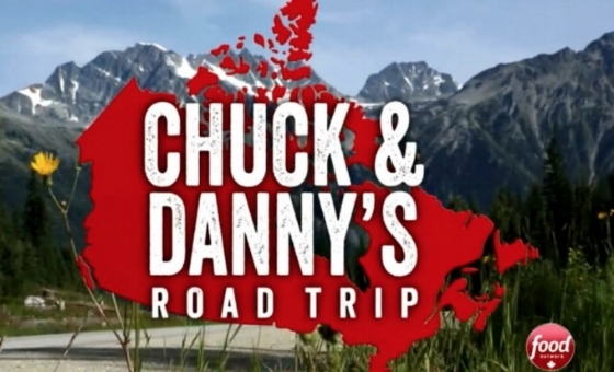 "The title ""Chuck & Danny's Road Trip"" is in white block letters against a red map of Canada. A road leading to the Rocky Mountains is in the background, and the round red and white Food Network Canada logo is in the lower right corner."