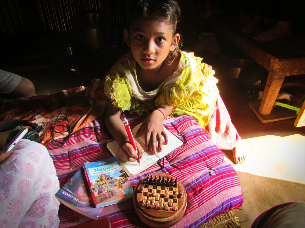 8 year old Nambrita takes notes during a chess lesson in her temporary home in Agara. Her family has been hosting Good Earth and Expansion Nepal members during the preparation and initial building days before the holiday break of Darshain.