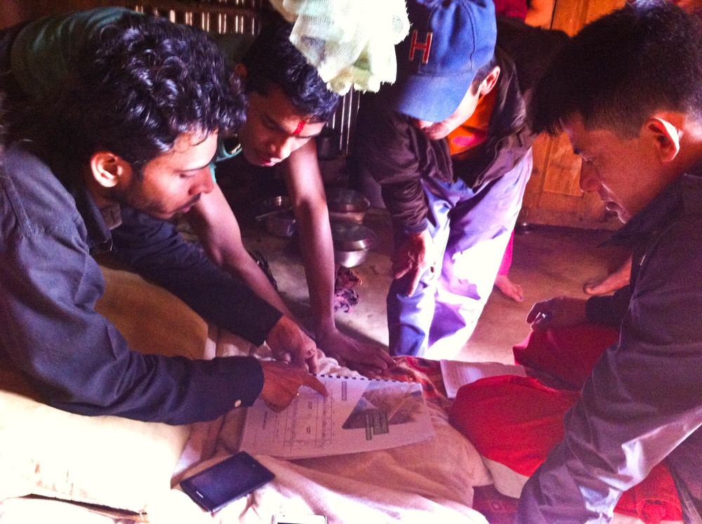 Expansion Nepal discussing wooden roof plans and work agreements with Agara community members.