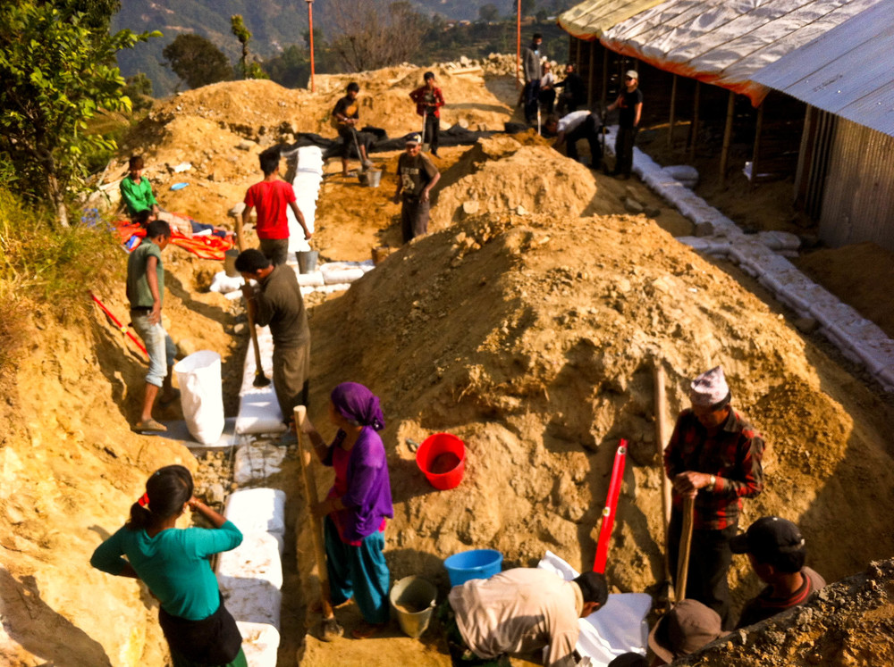 Villagers of Agara pick up the tools and skills quickly as the building team moves forward into the first couple earthbag courses, a huge relief after smashing the foundation gravel by hand for a week.
