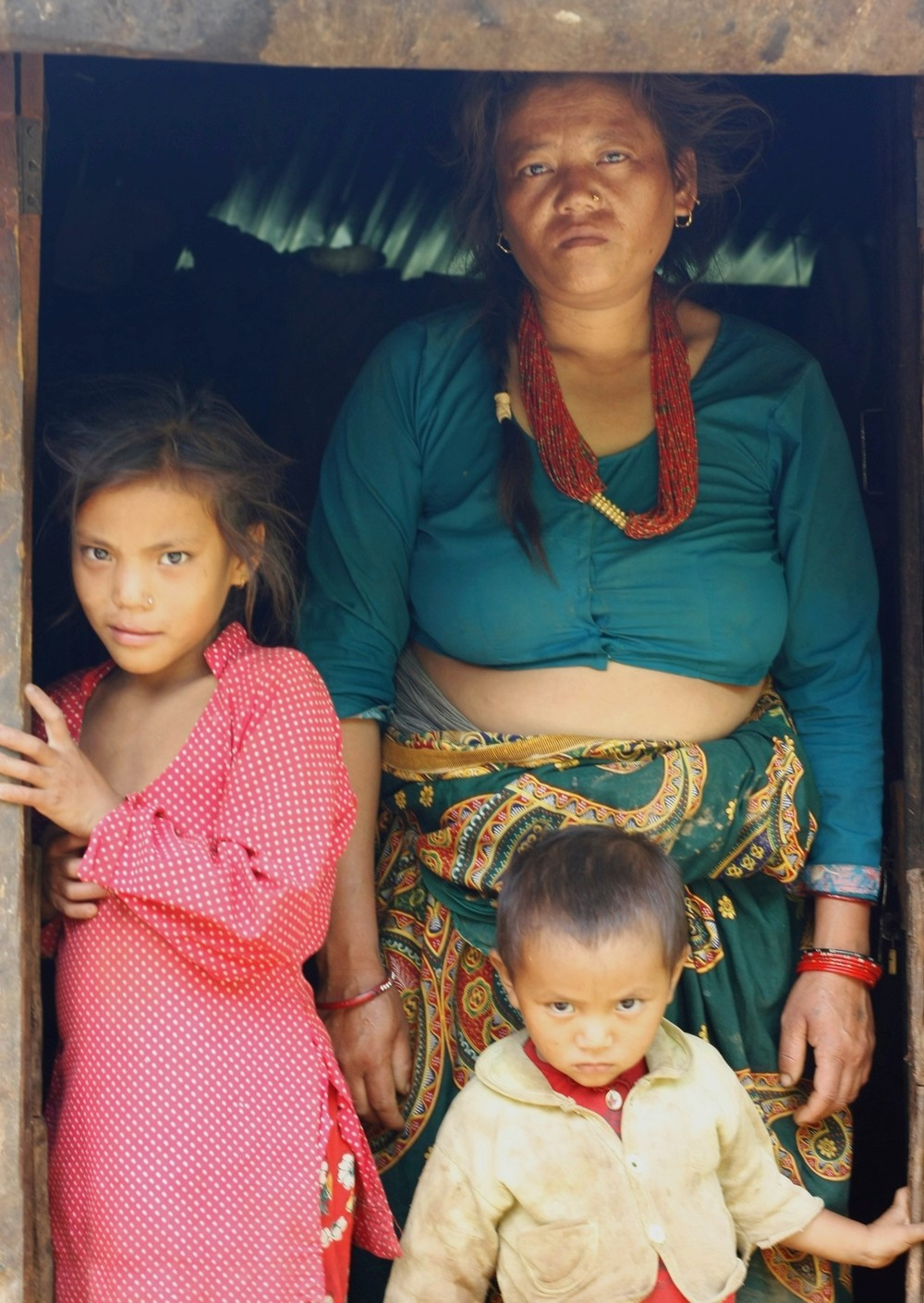 Dil Maya Tamang and two of her children in the doorway of their shelter.