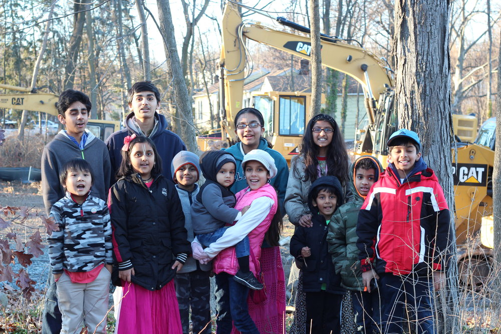 Children gather in front of a row of construction machines on December 25, 2016.  This temple is a gift for our children and generations to follow.