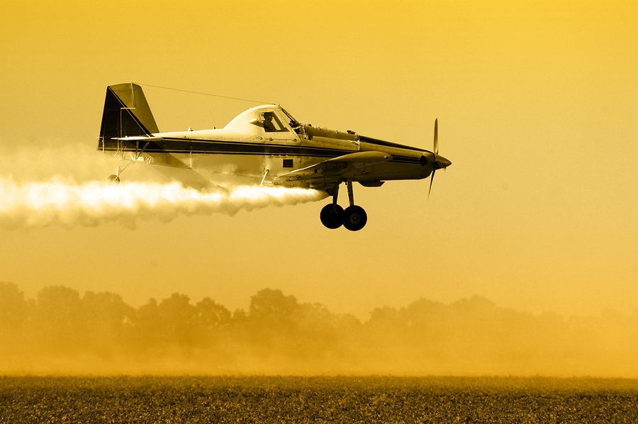Plane dropping pesticides and herbicides on crops.
