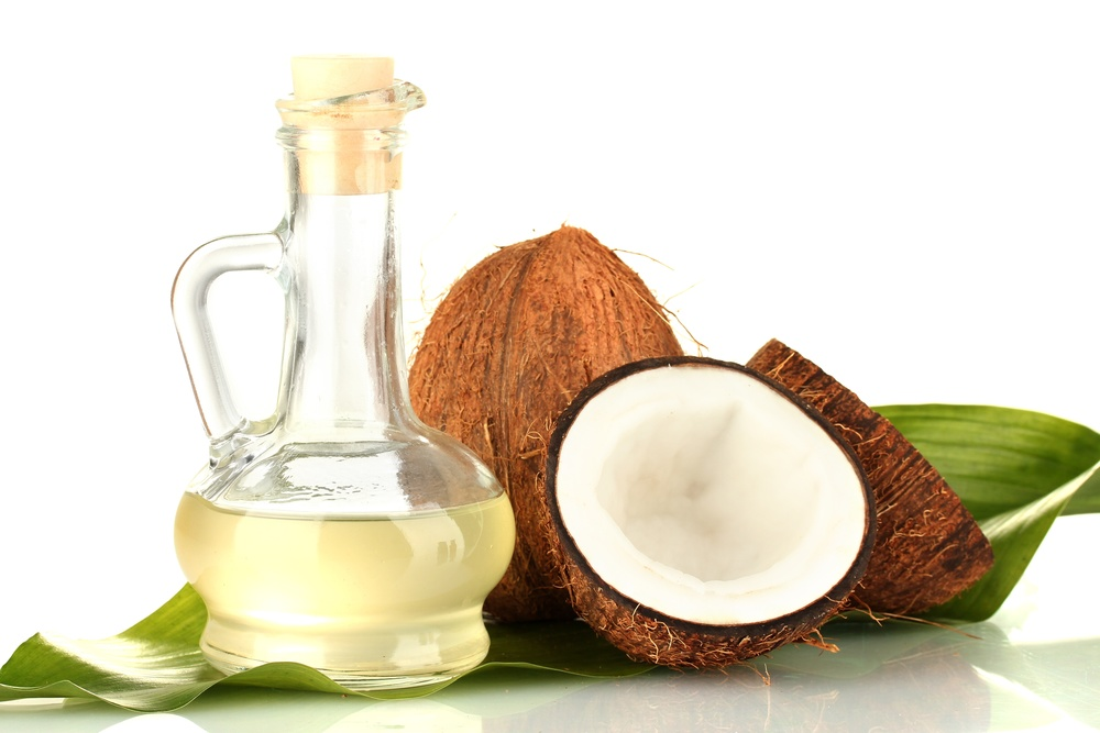 Coconuts and glass of coconut oil.
