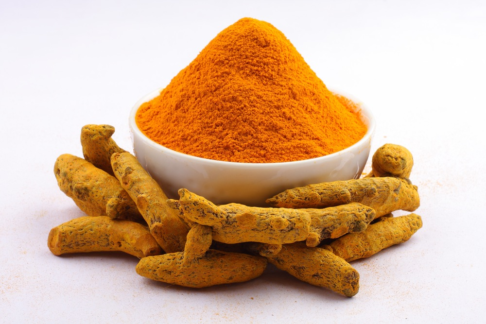 Whole turmeric and a bowl of turmeric powder. Curcumin is the main medicinal compound in turmeric.