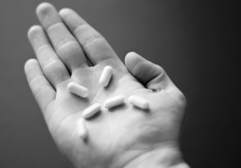 A person holding several psychiatric drugs in their hand.