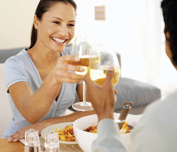 Woman smiling and clinking wine glasses with man.