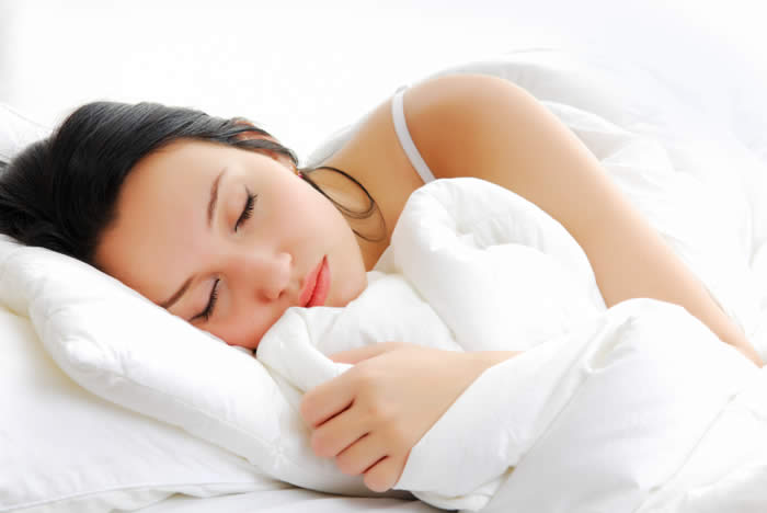 A woman is sleeping. Sleep can lower your cortisol levels.