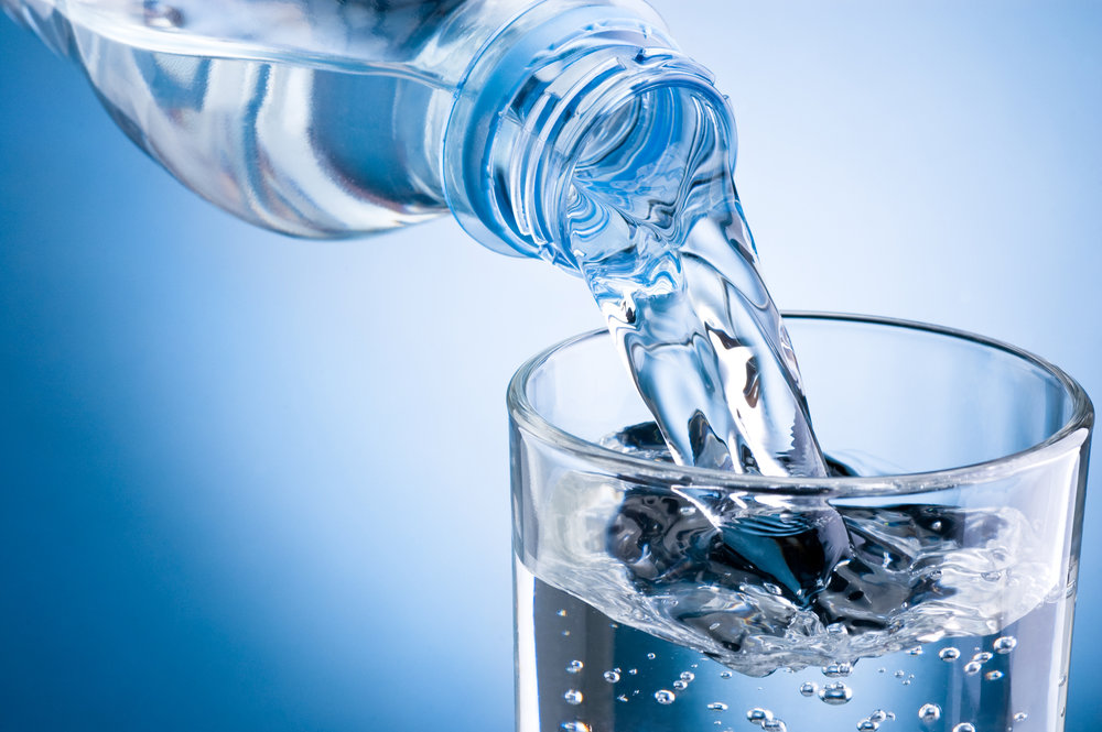 Water from a water bottle being poured into a glass. Drinking enough water can reduce stress and lower cortisol levels.