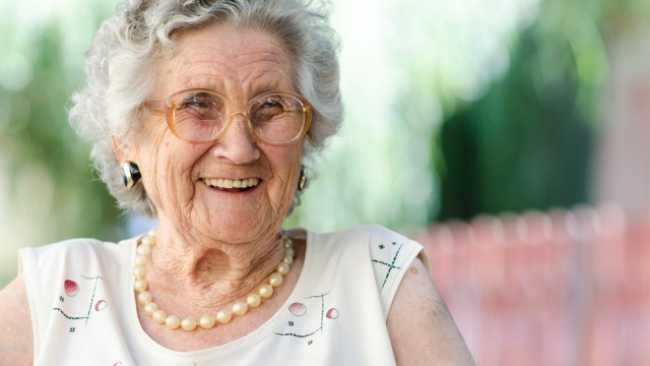 An elderly woman smiling.