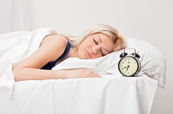 A woman sleeping in bed next to a clock. Deep sleep and melatonin can help prevent and reverse dementia and cognitive decline.