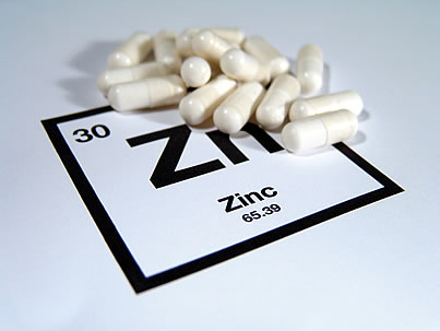 Zinc symbol and zinc supplement capsules. A zinc deficiency can contribute to the development of cognitive decline and dementia.