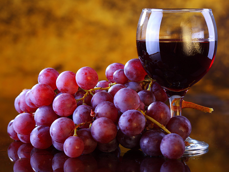 Glass of red wine and red grapes. Resveratrol is an antioxidant in red grapes and red wine, and it has been shown to help prevent and reverse cognitive decline and dementia.
