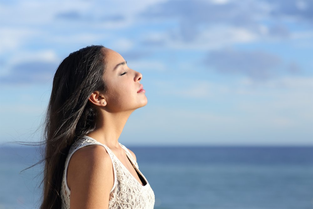 A woman closing here eyes and breathing deeply near the ocean. Deep breathing stimulates the vagus nerve.