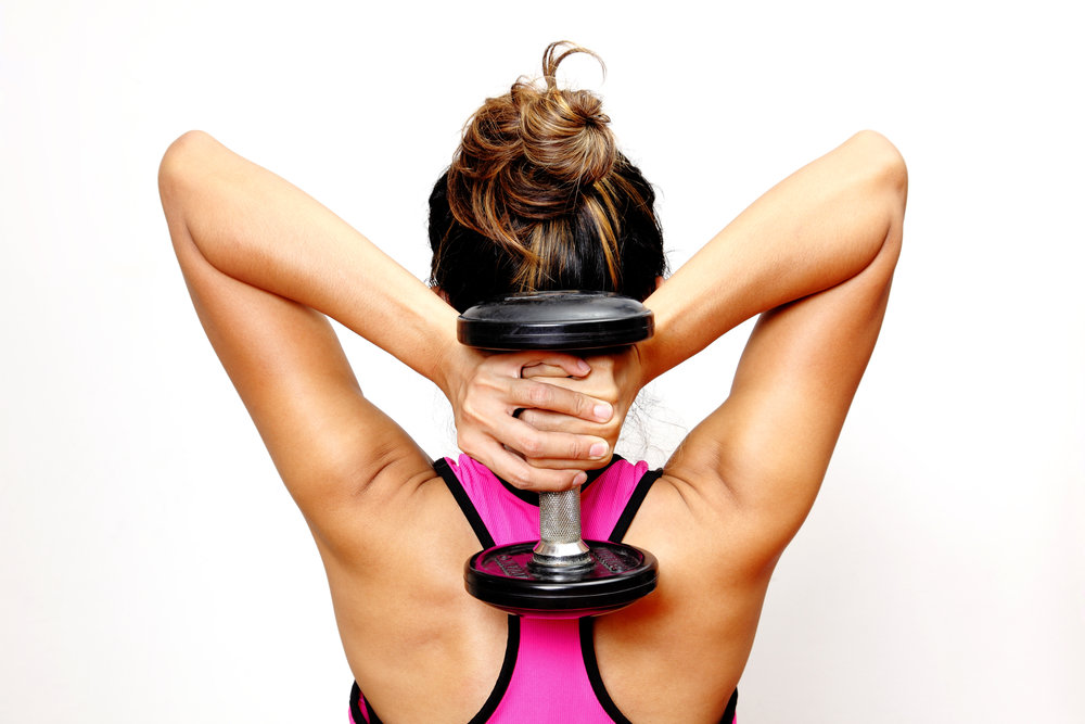 Woman lifting weights. Exercise can help with the regeneration of myelin.
